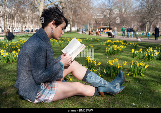 Young woman reading a book in St James's Park, London, England, UK - Stock Image