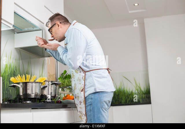 Side view of man tasting food while cooking in kitchen - Stock Image