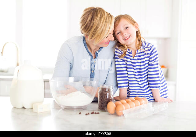 Portrait of girl (4-5) spending time with mom in kitchen - Stock Image