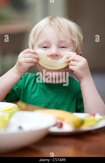 Boy playing with slice of melon at table - Stock Image