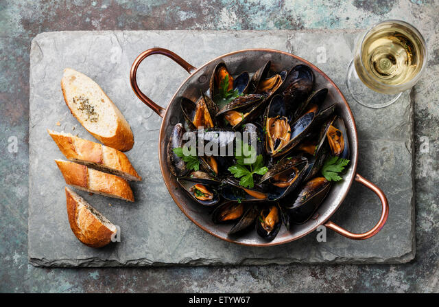 Mussels in copper cooking dish and French Baguette with herbs on stone slate background - Stock Image