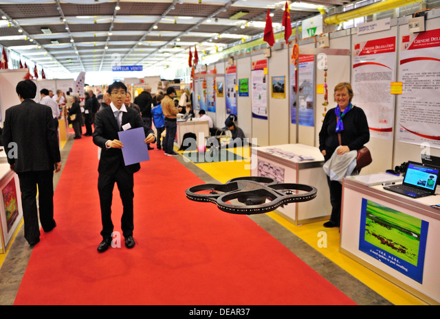 A Chinese inventor demonstrates a drone at the 2013 Geneva Inventors' Fair whilst a spectator looks on - Stock Image