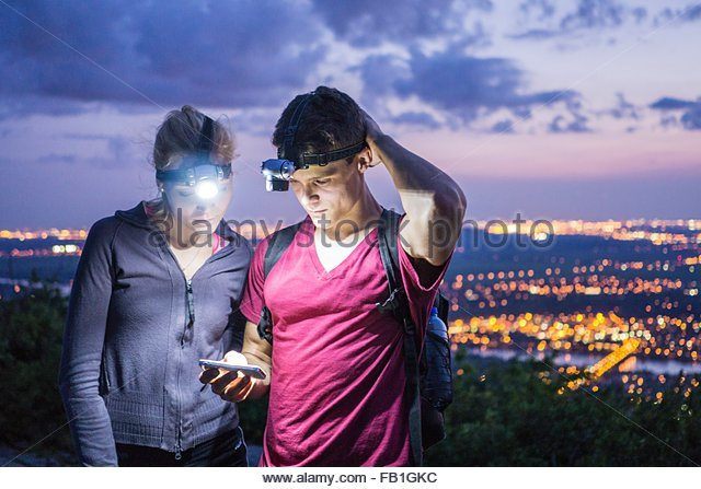 Young couple outdoors at night, wearing head lamps, looking at smartphone - Stock Image