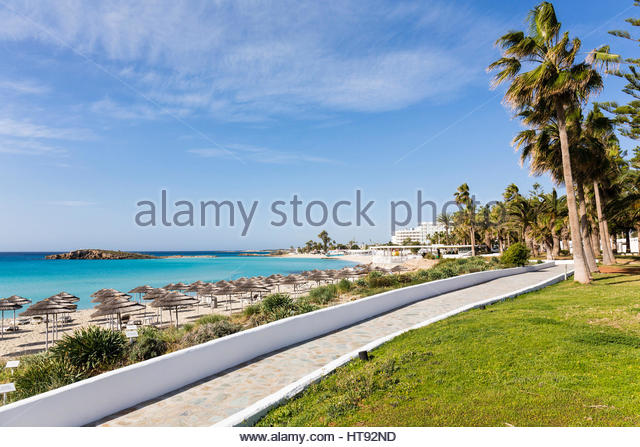 Beach umbrellas on Nissi Beach at the Nissi Beach Resort with stone walkway in Agia Napa, Cyprus - Stock Image