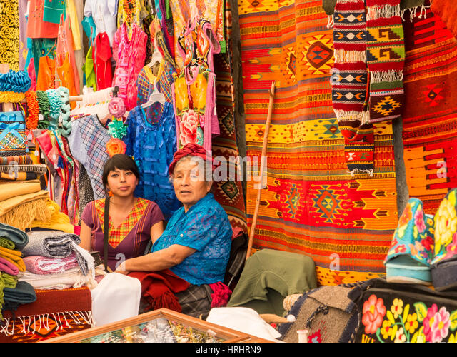 Women talking in market with background of handmade rugs and clothing, Oaxaca, Mexico, North America - Stock-Bilder