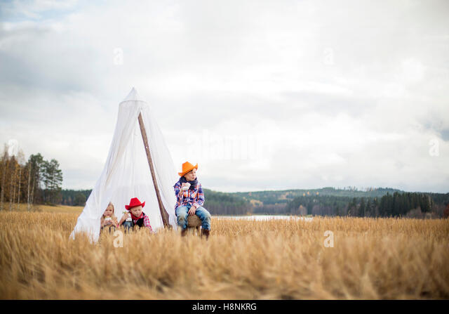 Children (8-9) wearing cowboy hats sitting in tent - Stock Image