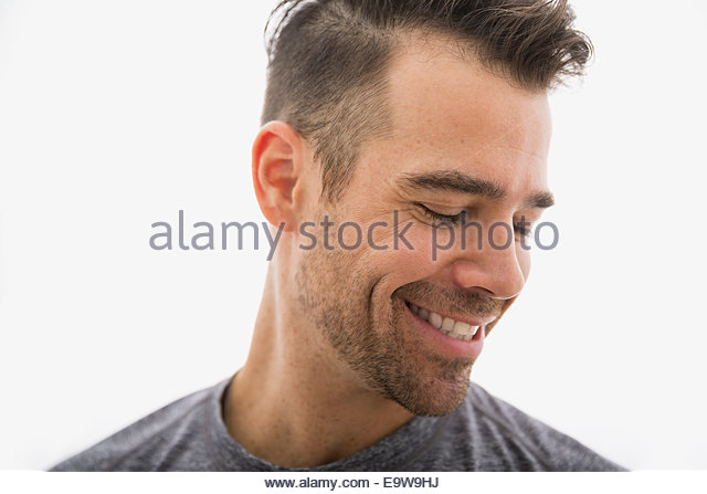 Close up of smiling brunette man looking down - Stock-Bilder