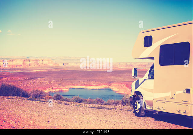 Vintage toned RV (camper) parked by canyon, family vacation concept, Lake Powell, USA. - Stock Image