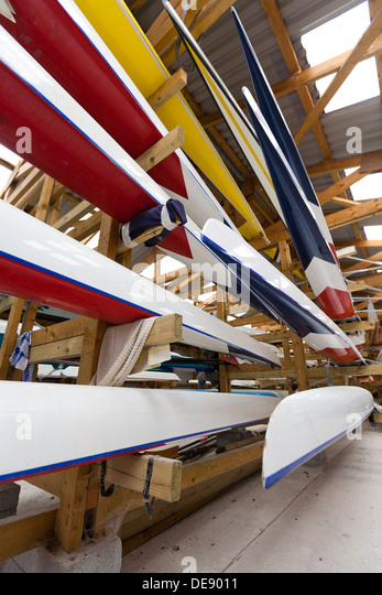 Low, wide-angle view of boats stored inside a rowing club boathouse - Stock Image
