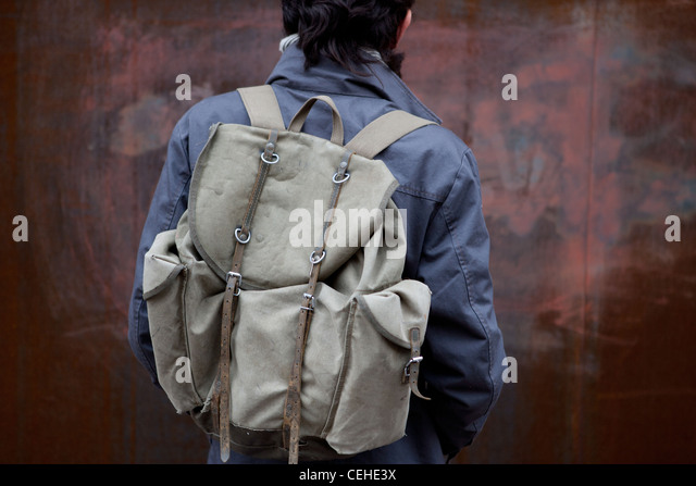 Young college student wearing a khaki backpack outdoors. - Stock Image