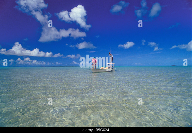 Bahamas andros island bonefishing guide and angler in clear shallow saltwater sand flats - Stock Image