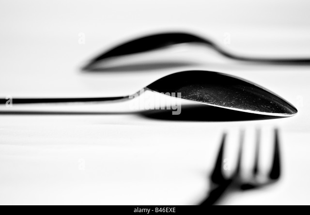 two spoons and a fork on a white table - Stock Image