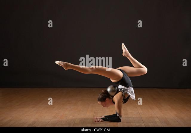 Gymnast bending backwards, balancing ball with head - Stock Image