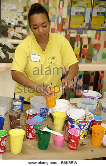 Miami Florida Overtown Hands on Miami Day volunteers community event Citrus Grove Middle School painting Black woman - Stock Image