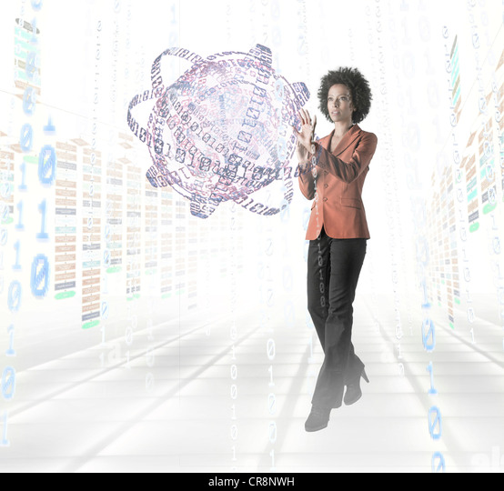 Businesswoman standing amidst digital objects - Stock Image