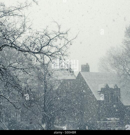 Wintertime snow falling with church in background - Stock Image