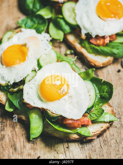 Healthy breakfast sandwiches on wooden board background - Stock Image