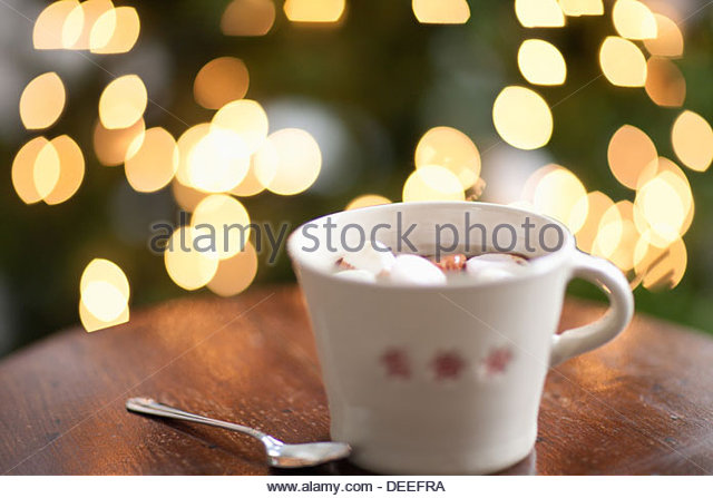 Mug of hot cocoa, Christmas tree in background - Stock Image