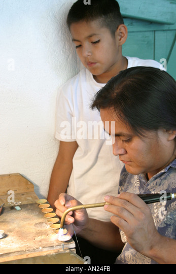 Albuquerque New Mexico State Fair Navajo Native Americans Indian Village father teaches son jewelry making T - Stock Image