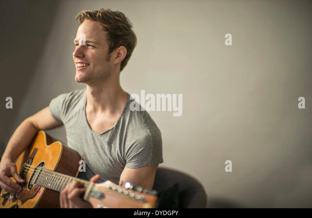 A beautiful young man playing acoustic guitar. - Stock Image