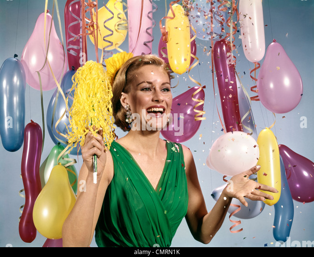 1960 1960s RETRO PARTY NEW YEAR BALLOONS WOMAN STREAMERS DRESS HAPPY - Stock Image