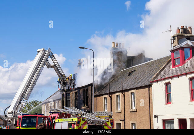 Scottish Fire and Rescue Service firefighters up a ladder tackling a burning house roof. Elie and Earlsferry Fife - Stock Image