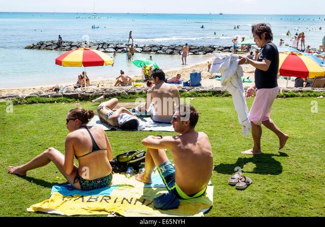 Hawaii Hawaiian Honolulu Waikiki Beach resort Kuhio Beach State Park Pacific Ocean sunbathers man woman couple - Stock Image