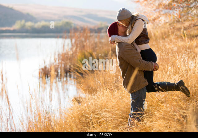 lovely young couple kissing outdoors in autumn - Stock Image