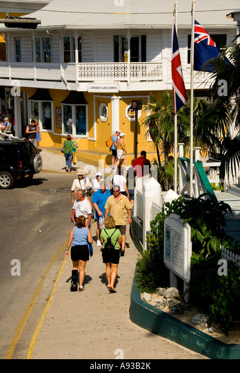 George Town Grand Cayman tourists walking along waterfront - Stock Image