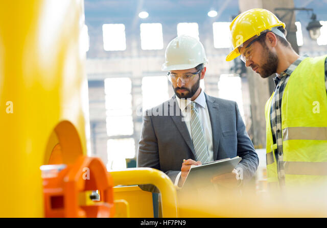 Manager and steel worker examining equipment in factory - Stock Image