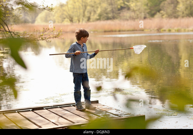 Boy standing on pier and fishing in river - Stock Image