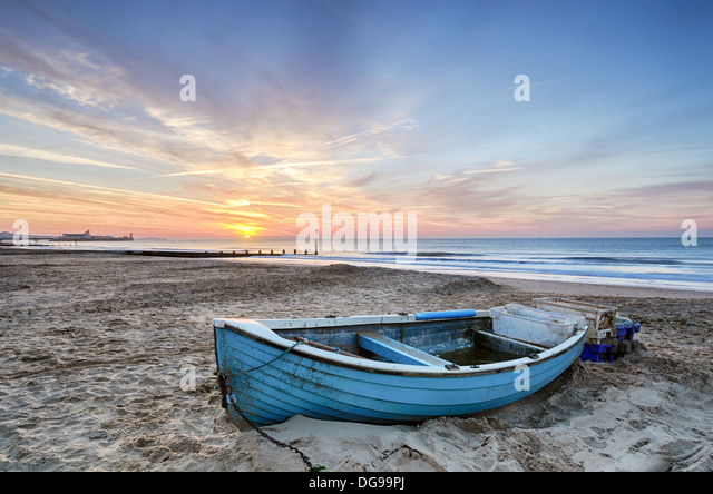 Turquoise blue fishing boat at sunrise on Bournemouth beach with pier in far distance - Stock-Bilder