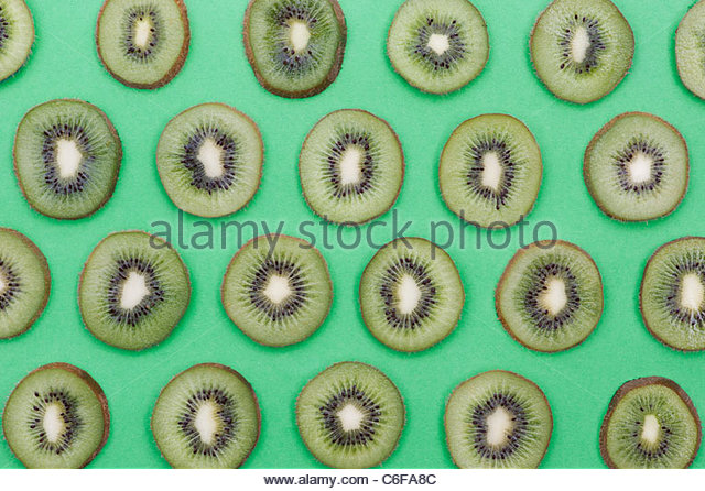Actinidia deliciosa. Kiwifruit slices on green background. Chinese gooseberry. Food pattern. - Stock Image
