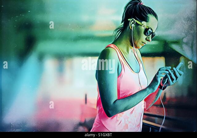 Woman with earphones touching the smartphone - Stock-Bilder