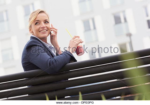 Business woman having lunch break on park bench - Stock Image