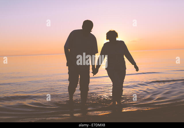 Senior couple walking at sunset - Stock Image
