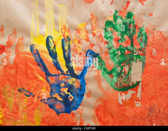 Impression of hands made with paint on brown paper - Stock Image