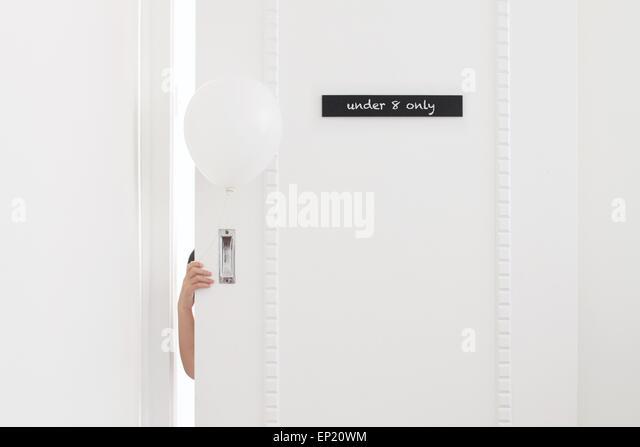 Boy holding a balloon and hiding behind a door - Stock Image