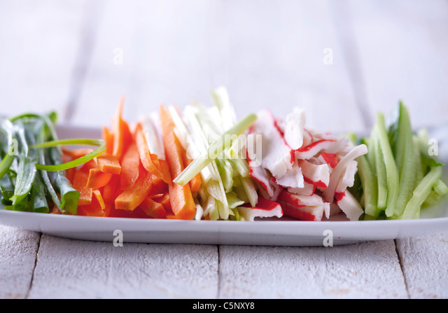 Stripes of chive, carrot, leek, surimi and cucumber - Stock Image