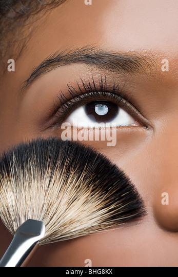 Woman with makeup brush near eye - Stock Image
