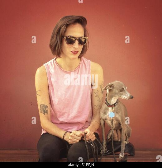 Tattooed Woman with Italian Greyhound - Stock Image