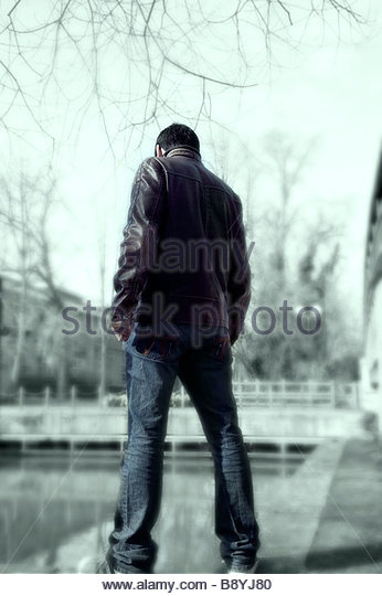 man deep in thought looking into a lake - Stock-Bilder