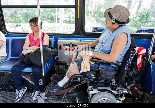 Lower Manhattan New York City NYC NY Chinatown MTA public transportation bus electric wheelchair disabled man passenger - Stock Image