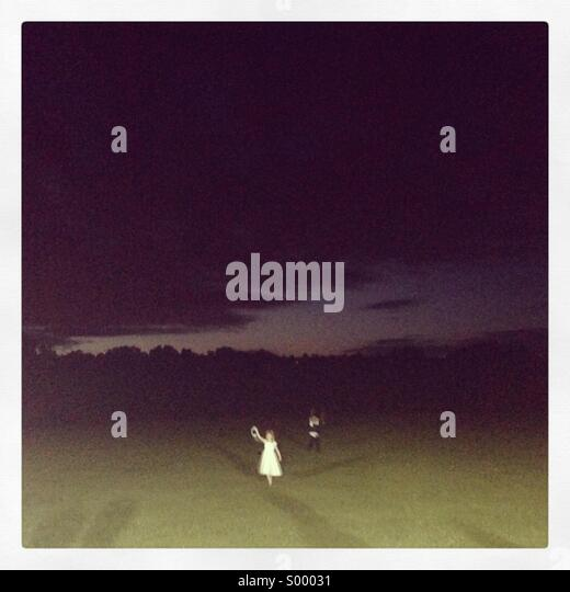 Creepy kids in a field at night - Stock Image