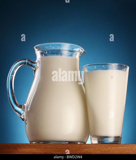 Glass and jar of milk on a blue background. - Stock Image