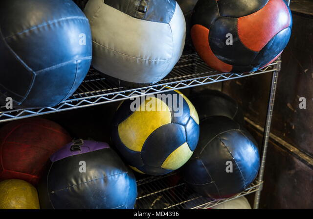 Medicine balls on metal shelf in gym, close-up - Stock Image