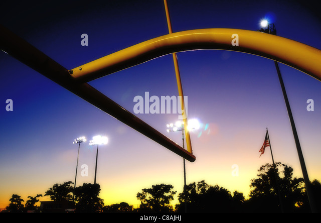 American football goalpost at dusk, with silhouetted tree line and US flag - Stock Image