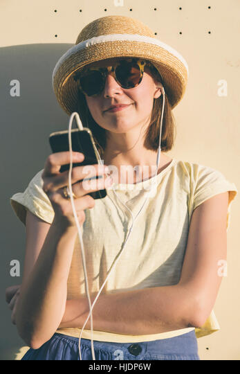 Beautiful young hipster Caucasian woman with smartphone and earphones, texting and listening to music. Happy teenage - Stock Image