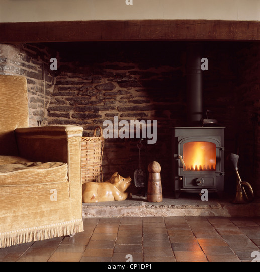 Upholstered sofa in front of woodburning stove in inglenook fireplace - Stock Image