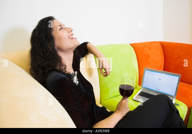 woman lady girl on multicolor couch furniture laptop screen holding wine laughing white green orange black comfort - Stock Image
